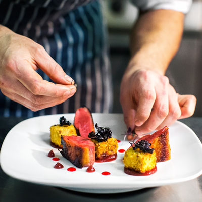 chef preparing food being laid out on a plate in the kitchen